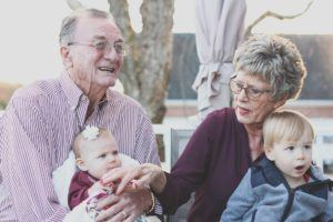 elderly man and woman holding their two grandchildren