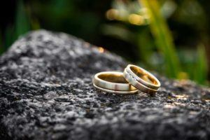 close up shot of two gold rings sitting on rock