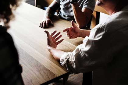 group of people sitting at wooden table with one gesturing towards group with both hands