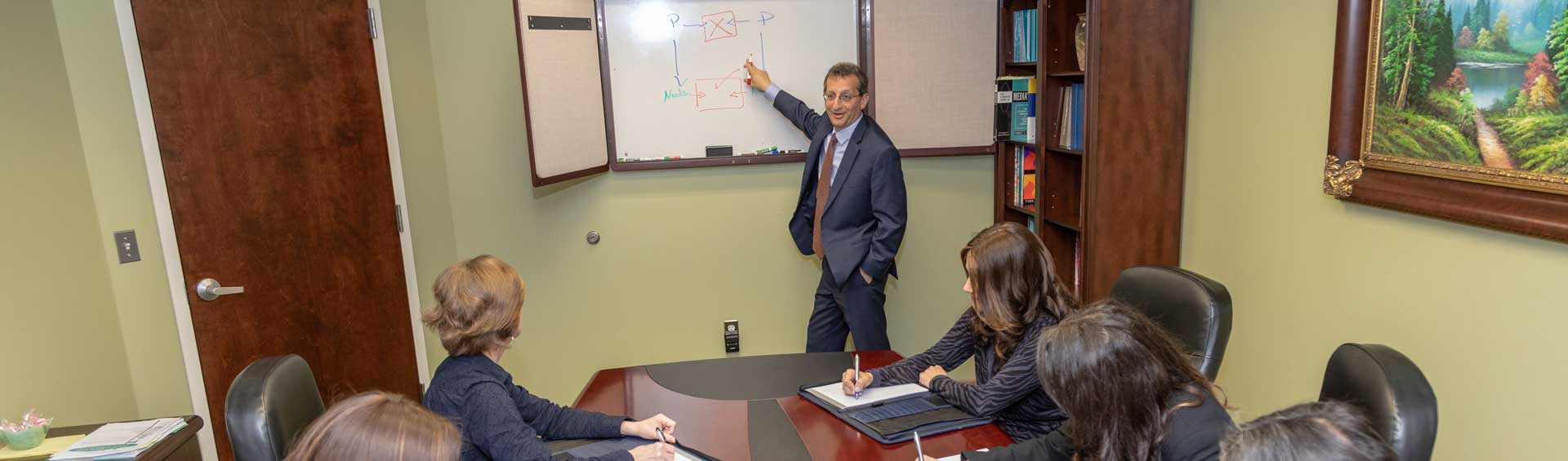 adam berner gesturing towards white board in conference room with team at desk writing in notebooks