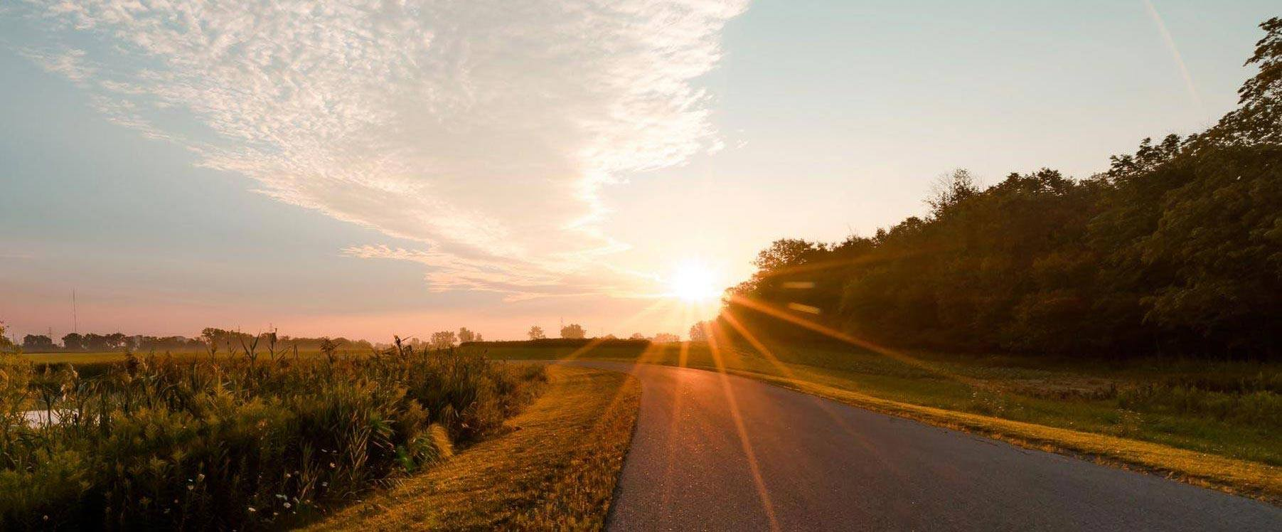 rural road with sun setting on the horizon