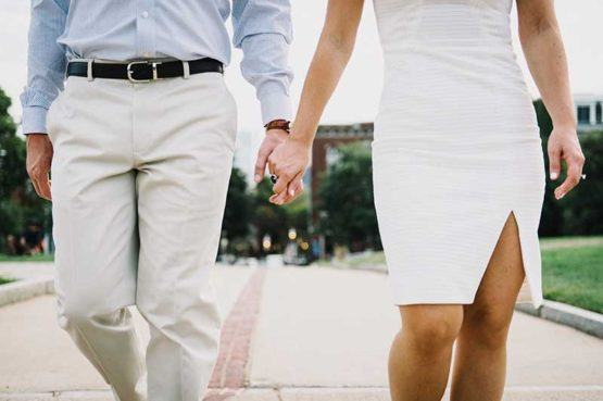 man in dress pants and shirt walking and holding hands with woman in white dress